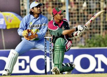 CHITTAGONG, BANGLADESH:  Bangladesh cricket captain Habibul Bashar (R) hits a boundary as Indian wicketkeeper M.S. Dhoni (L) looks on during the first One Day International (ODI) match between Bangladesh and India at the M.A Aziz Stadium in Chittagong, 23 December 2004. Bangladesh, who are chasing an Indian total of 245 runs, have scored 196 runs for the loss of seven wickets in the 48th over. AFP PHOTO/Farjana K. GODHULY  (Photo credit should read FARJANA K. GODHULY/AFP/Getty Images)